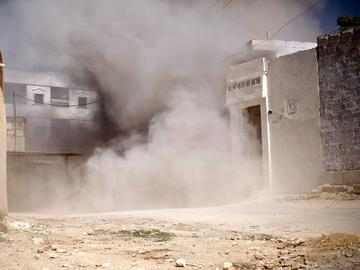 A street is choked with dust and debris from an exploding shell fired by government tanks that have advanced into Saraquib city on April 9, 2012 in Syria.