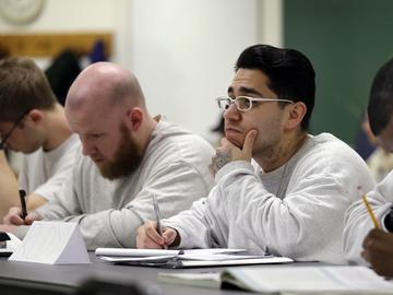 In this photo taken Thursday, Jan. 28, 2016, Rudy Madrigal, center, looks on as he sits with fellow inmates in a a college world history class at the Monroe Correctional Complex in Monroe, Wash.