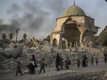 Fleeing Iraqi civilians walk past the heavily damaged Al Nuri mosque in the Old City of Mosul, days before Iraqi forces announced victory.