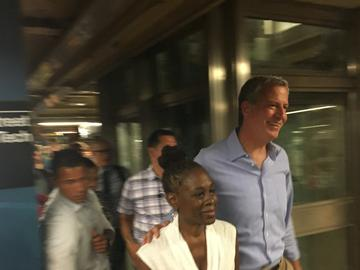 With dozens of reporters and photographers racing to keep up, Mayor de Blasio and his wife, Chirlane McCray, make their way from the F train to a campaign event.