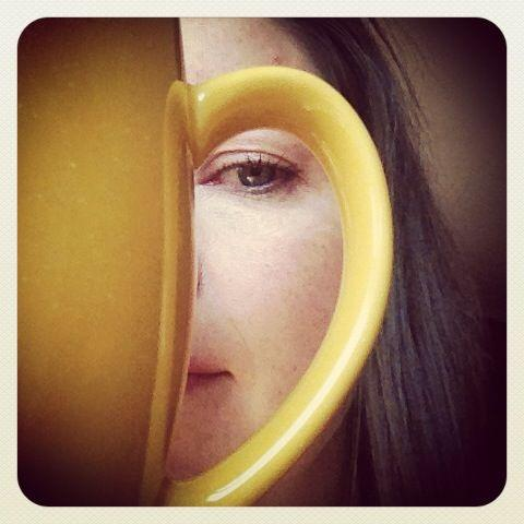woman framed by coffee mug