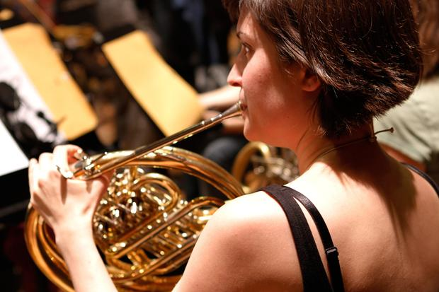 A French horn-playing member of the Brooklyn Philharmonic during a rehearsal at the DiMenna Center.