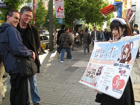 Kurt and Roland spot a young woman advertising a nearby maid cafe.