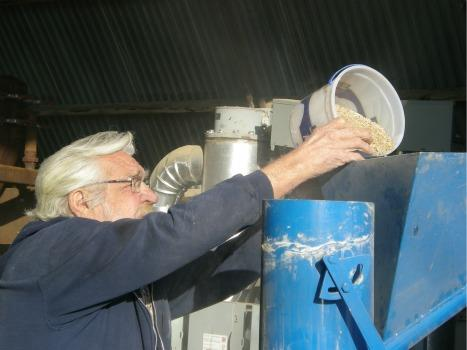 Frank Polifka loads whole wheat into a smaller version of the Windhexe.