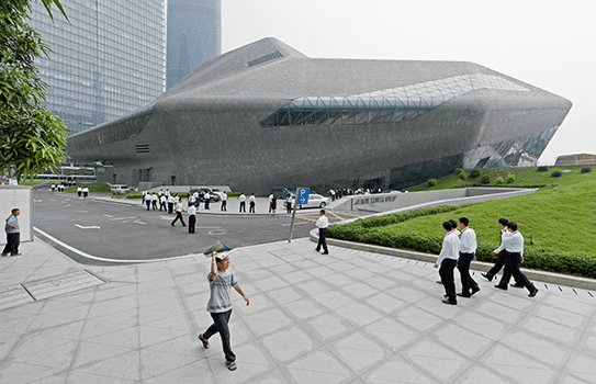 The Guangzhou opera house is just as unconventional on the outside, perching on a patch of grass like a spaceship that's just touched down.