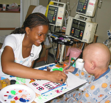 An art therapy student paints with a patient as part of Shands Hospital's Arts in Healthcare program in Gainesville, Florida. Bringing the arts into hospital settings helps to humanize healthcare and