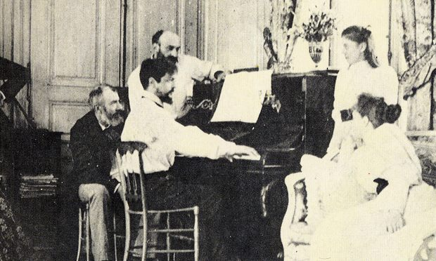 Claude Debussy at the piano in front of the composer Ernest Chausson in 1893.