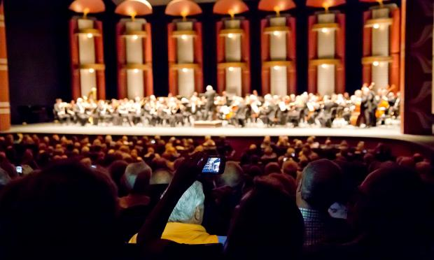 Detroit Symphony Orchestra patrons take photos at a concert in Florida