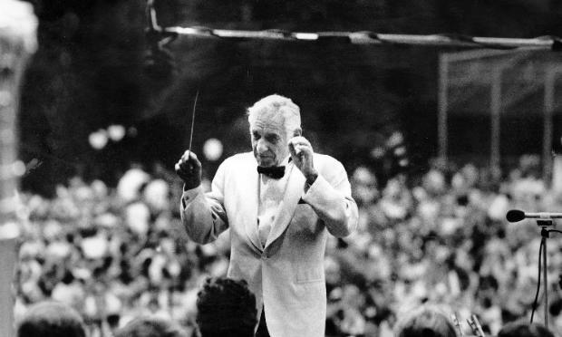 Leonard Bernstein pauses as he faces members of the New York Philharmonic on the Great Lawn in Central Park