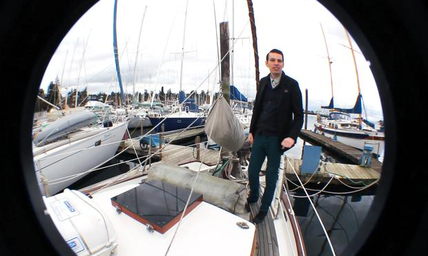 Musician and composer Jherek Bischoff stands on the boat he grew up on near Seattle, Wash.