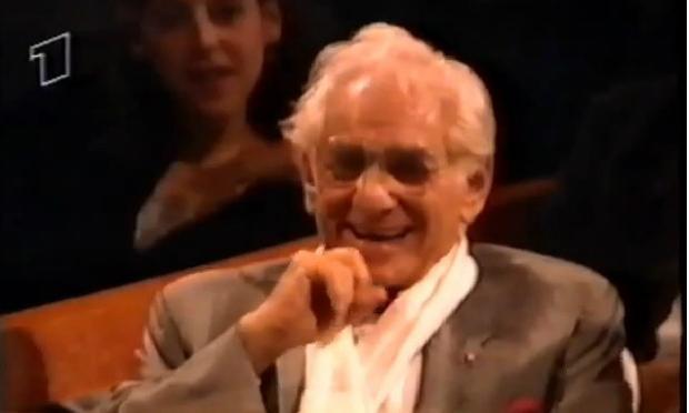 Leonard Bernstein laughs as Lauren Bacall serenades him in 1988