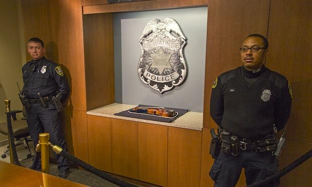 Two police officers stand guard over the recovered 300-year-old Stradivarius violin that was taken from the Milwaukee Symphony Orchestra's concertmaster in an armed robbery last week February 6, 2014