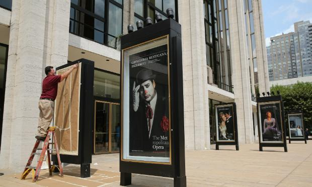 A worker unveils advertisement for future productions at the Metropolitan Opera.
