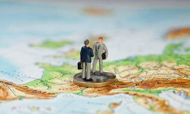 Two miniature figurines of businessmen shaking hands standing on a Euro coin on a map of Europe.