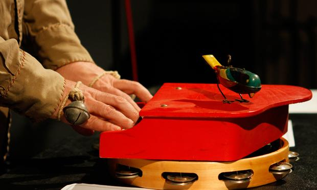 Stephin Merritt plays a toy piano, on top of a tambourine, with a mechanical toy bird.