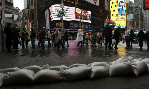 People walk by sand bags in front of a building in Times Square as Hurricane Sandy arrives