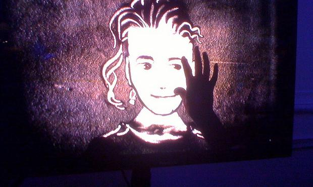 face drawn in sand, lit up from behind, artists hand in picture