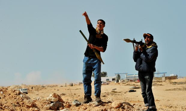 Libyan rebel fighters hold a rocket propelled grenade launcher (RPG) as a pro Kadhafi fighter jet fly over the eastern oil port city of Ras Lanuf on March 11, 2011.