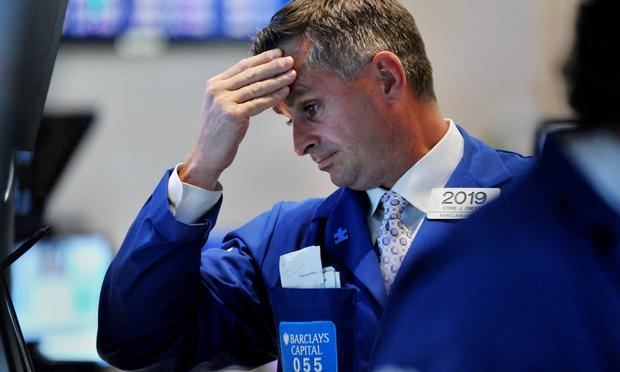 A trader reacts to the market downfall on the floor of the New York Stock Exchange at the closing bell August10, 2011.