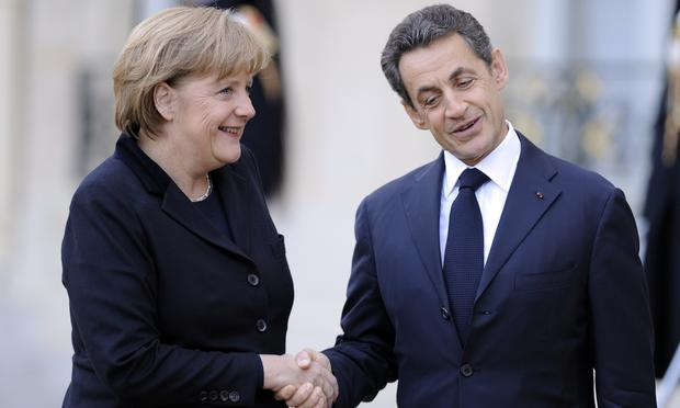 French President Nicolas Sarkozy (R) shakes hand with German Chancellor Angela Merkel after their meeting at the Elysee palace on December 5, 2011 in Paris