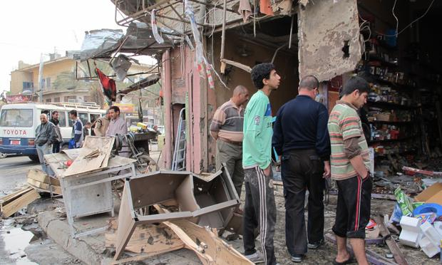 Iraqis inspect the damage after a wave of attacks in Baghdad killed at least 57 people on December 22, 2011. The apparently coordinated blasts were the first major sign of violence since US withdrew.