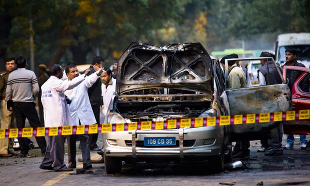 Police and forensic officers examine a damaged Israeli embassy vehicle after an explosion on February 13, 2012 in New Delhi, India.