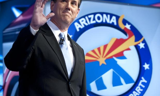 Republican presidential candidate Rick Santorum waves as he arrives to the debate hall on February 22, 2012 in Mesa, Arizona.