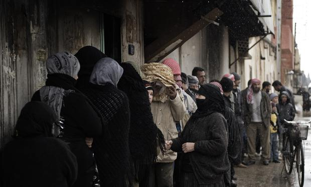 Syrians queue for bread outside a bakery in Qusayr, 15 kms (nine miles) from Homs, on March 1, 2012. Syrian rebels were still holding out more than 24 hours into a ground assault by regime forces aga