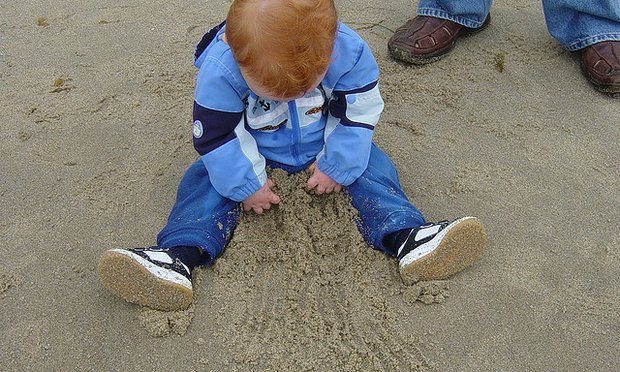 baby playing in a sandbox