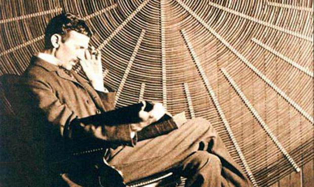 Nikola Tesla in front of the spiral coil of his high-frequency transformer in New York.