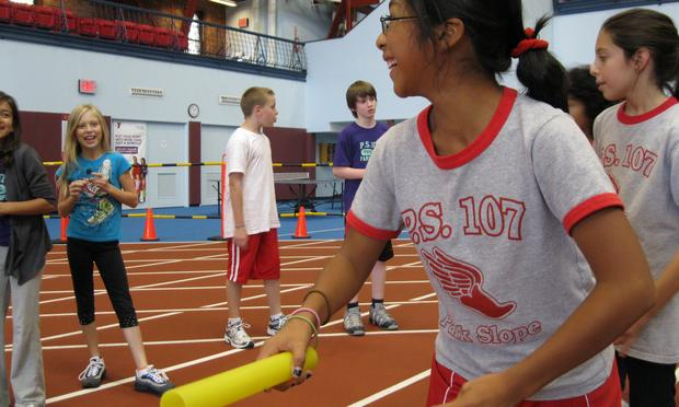 A girl lines up to run carrying a baton wearing a PS107 tshirt