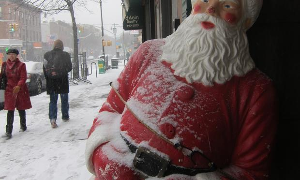 A Santa figurine receives a coating of snow in Brooklyn Sunday as a post-Christmas storm sweeps through the area.