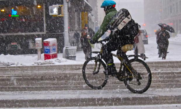 Rain or snow or freezing fog, a New York City bicycle messenger cuts through the slush along 7th Avenue in Manhattan.