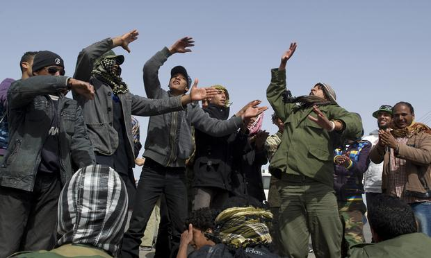 Libyan rebellion supporters perform a song to cheer fighters heading to the frontline from the eastern town of Ajdabiya on April 6, 2011.