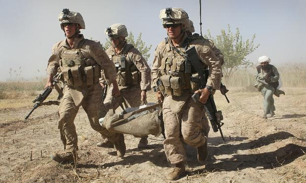 U.S. Marines carry a wounded enemy prisoner of war (EPW) to a MEDEVAC helicopter September 21, 2010 near Marja, Afghanistan.