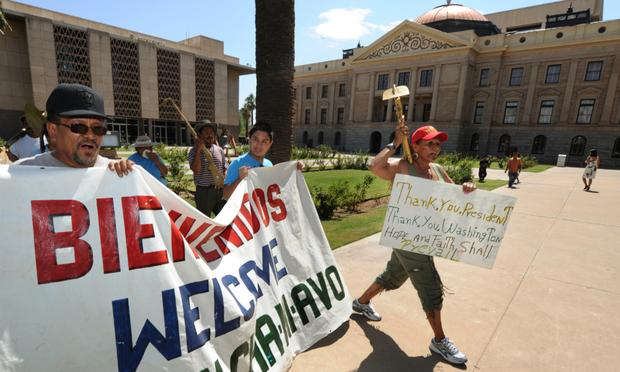 Protesters march past the Arizona State Capital Building as they campaign against the controversial state law SB1070
