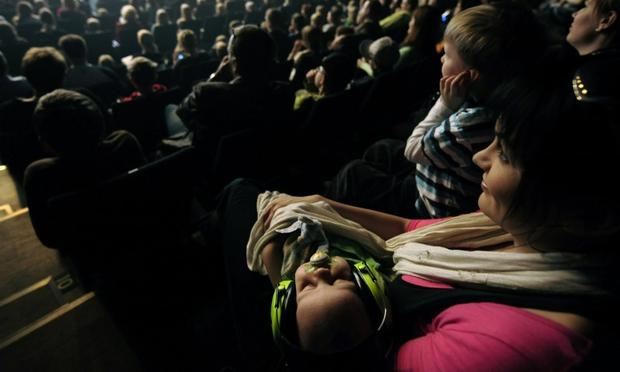 A two-month-old baby wears ear muffs for hearing protection while sleeping during the concert