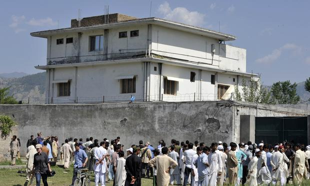 Pakistani media personnel and local residents gather outside the hideout of Al-Qaeda leader Osama bin Laden following his death by US Special Forces in a ground operation in Abbottabad on May 3, 2011.