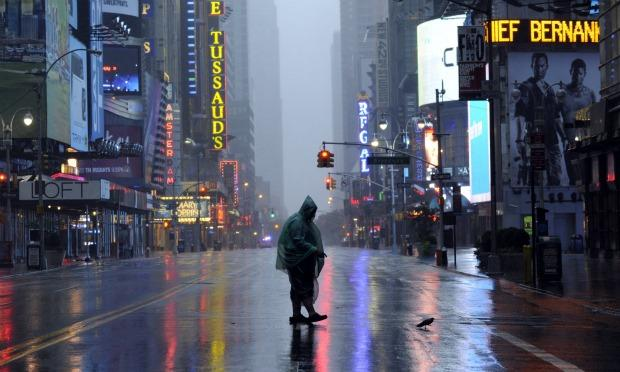 A man walks across 42nd Street in Times Square in New York on August 28, 2011 as Hurricane Irene hits the city and Tri State area with rain and high winds.