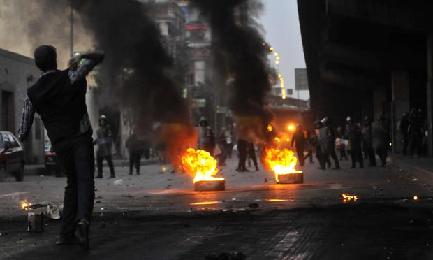 Egyptian riot police gather near burning tires as a demonstrator throws an object towards them during a protest in Cairo, Egypt on January 26, 2011