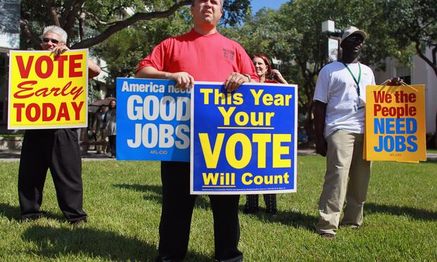 Jason Joseph  holds campaign signs during a get out the vote rally put on by local unions and Democratic politicians on the grounds of the Jackson Memorial hospital on October 18, 2010 in Miami, Fla.