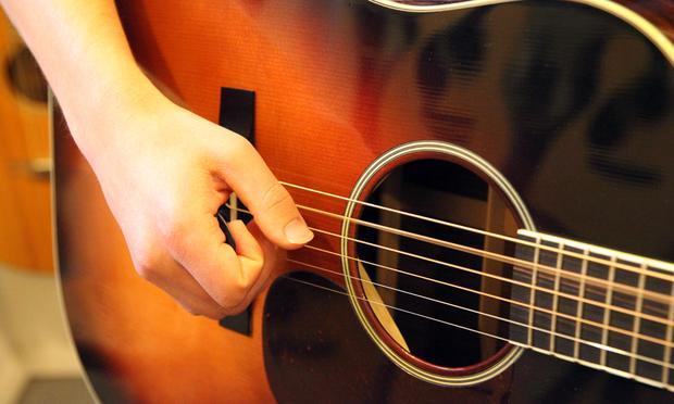 Joe Fox strumming a guitar at Mandolin Brothers.