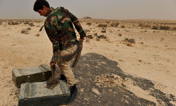 A Libyan rebel fighter prepares an ammunition belt on the outskirts of Ras Lanuf on March 4, 2011 before heading with a group of comrades into the oil port town to battle Moammar Gadhafi loyalists.