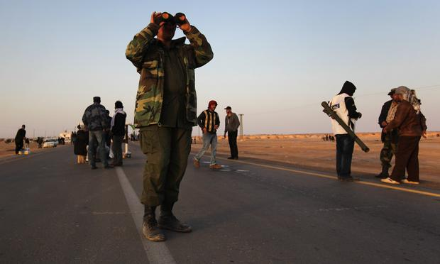 A rebel fighter scans the horizon for government troops on March 3, 2011 in Ajdabiya, Libya.