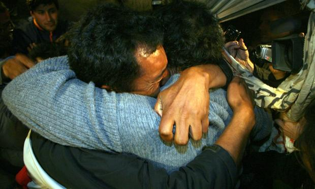 Alfonso Avalos(R) father of Chilean miner Florencio Avalos and Wilson Avalos brother of Florencio embrace each other after Florencio was brought to the surface