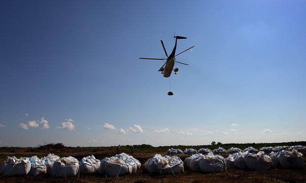 A Louisiana National Guard helicopter carries away sandbags as it takes part in an operation to fortify offshore barrier islands from incoming oil June 1, 2010