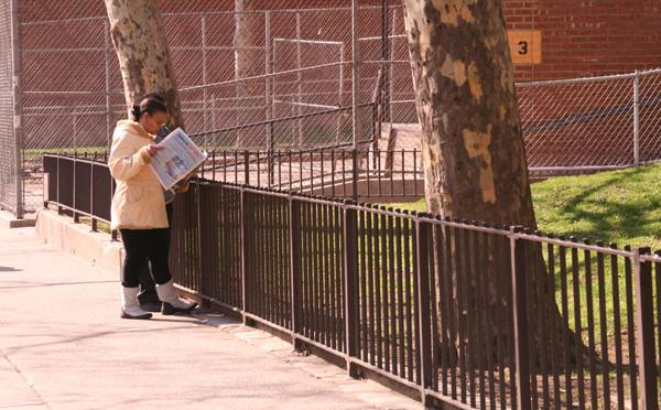 A woman reads the paper near the Grant housing project