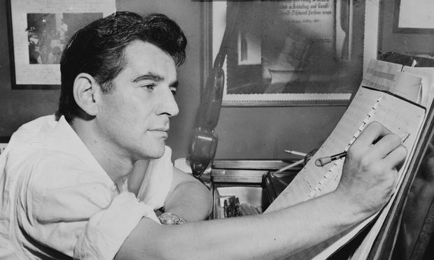 Leonard Bernstein seated at the piano in 1955.