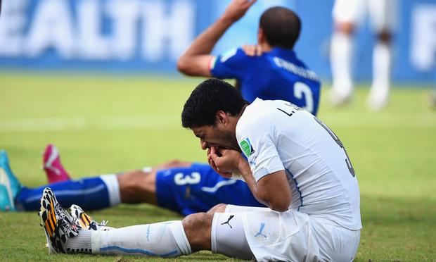 Luis Suarez of Uruguay and Giorgio Chiellini of Italy react after a clash during the 2014 FIFA World Cup Brazil Group D match at Estadio das Dunas on June 24, 2014 in Natal, Brazil.