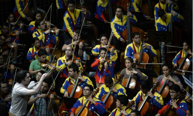 Gustavo Dudamel conducts the Simon Bolivar Symphony Orchestra before the beginning of the swearing-in ceremony of the new ministers in Caracas, on April, 22, 2013.
